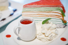 Rainbow crepe cake with a cup of strawberry juice Royalty Free Stock Photos
