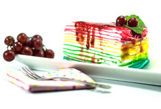 Rainbow crepe cake. Rainbow cake with grapes fork and napkin on white background Royalty Free Stock Image