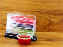 Rainbow crepe cake in plastic box and sweet strawberry sauce on wooden background Stock Images