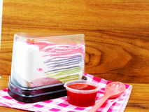 Rainbow crepe cake in plastic box and sweet strawberry sauce on wooden background Royalty Free Stock Photo