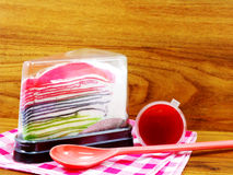 Rainbow crepe cake in plastic box and sweet strawberry sauce on wooden background Royalty Free Stock Images