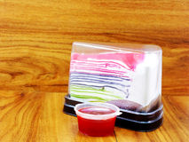 Rainbow crepe cake in plastic containning box and sweet strawberry sauce Royalty Free Stock Images