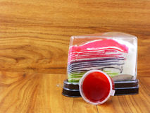 Rainbow crepe cake in plastic containning box and sweet strawberry sauce Royalty Free Stock Image