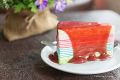 Rainbow crepe cake with strawberry sauce, selective focus Royalty Free Stock Image