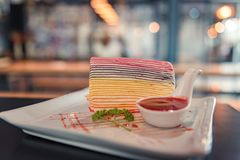 Rainbow crepe cake with strawberry sauce in white plate on wooden table, blur background. Rainbow crepe cake with strawberry sauce in white plate on wooden royalty free stock photo