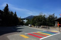 A rainbow crosswalk on a street in mountain village. royalty free stock photography