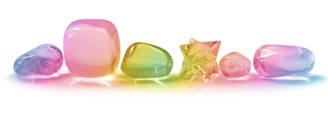 Rainbow Crystals on white background. A row of five tumbled stones and a merkabah with rainbow light on a white background stock photo