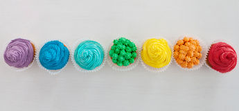 Rainbow cupcakes on the white background with copy space Stock Photography