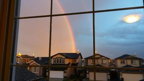 Seeing Rainbows from my Window. A rainbow cuts through the sky changing the blue clouds to pink Stock Images