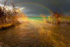 Rainbow and dark clouds over large lake Royalty Free Stock Images