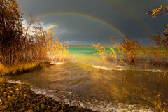 Rainbow and dark clouds over large lake Stock Photo