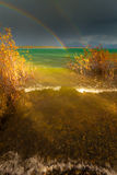 Rainbow and dark clouds over large lake Stock Photos