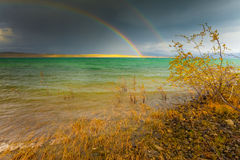 Rainbow and dark clouds over large lake Royalty Free Stock Photo