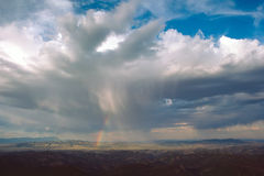 Rainbow in the Desert. Distant rainbow descending from thunderhead cloud to the desert royalty free stock image