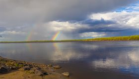 Rainbow double over the river stock photography
