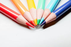 Rainbow drawing pencils with shavings on white. Rainbow colored drawing pencils with shavings on white paper Royalty Free Stock Images