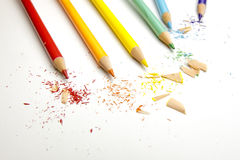 Rainbow drawing pencils with shavings on white. Rainbow colored drawing pencils with shavings on white paper Royalty Free Stock Photos