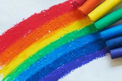A rainbow drawn with crayons and raindrops falling on it. Rainbow painted with red, orange, yellow, green, blue, dark blue, purple crayons and raindrops falling royalty free stock photography
