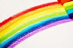 A rainbow drawn in pastel and pastels next to it. A rainbow drawn in pastel and the red,yellow,orange,green, blue, indigo, purple pastels next to it stock photo