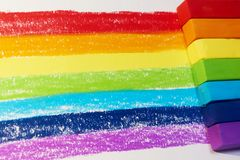 A rainbow drawn in pastel and pastels next to it. A rainbow drawn in pastel and the red,yellow,orange,green, blue, indigo, purple pastels next to it royalty free stock photo