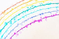 A rainbow drawn with a thin pen is spreading in the water. There are drops of water on a rainbow with crayons, and the pen`s ink is smudged by the water stock photo