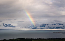 Rainbow at the end of the road. Rainbow comes down to touch Halibut Cove, Alaska Stock Images