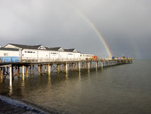 Rainbow at the End of Teignmouth Pier. A bright rainbow appears at the end of the historic Teignmouth Pier after a heavy shower, Devon, England Royalty Free Stock Photos