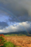 Rainbow ends in field after rain shower with no pot of gold, backdrop Maui mountains - Hawaii. Grey rain clouds stock photo