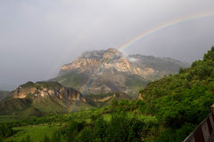 Rainbow in the evening after a rain in the mountains in the summer Stock Image