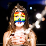 Rainbow face art. Portrait of young pretty girl royalty free stock photography