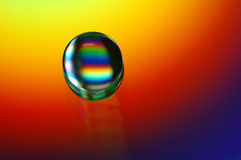 Rainbow factory. A water drop on compact disk royalty free stock photography