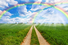 Rainbow field. Green field with rainbow and country road Stock Images