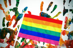 Rainbow flag. A rainbow flag on a background with handprints of differents colors stock photography