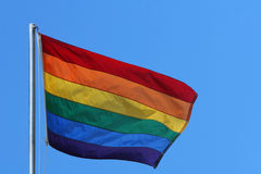 Rainbow flag. Flag in rainbow colors flying against a clear blue sky in sunny weather Stock Images