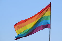 Rainbow flag against the blue sky. Symbol of tolerance and acceptance, diversity, hope and longing. The colors of this flag are specially for LGBT (Lesbian stock photography