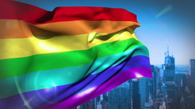 Rainbow flag blowing above city stock footage