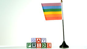 Rainbow flag blowing in the breeze beside gay pride blocks Stock Photo