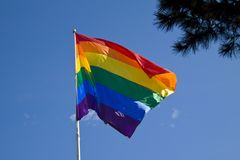 Rainbow flag with blue sky background - LGBT symbol - for gay, lesbian, bisexual or transgender relationship, love or sexuality. Stock image stock images