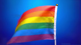 Rainbow flag, the LGBT flag, a gay pride flag waving in the wind against a blue background.  stock video footage