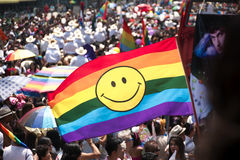 Rainbow flag. MEXICO CITY - JUNE 2, 2012: Rainbow flag with smiley face displayed during gay pride parade stock photo