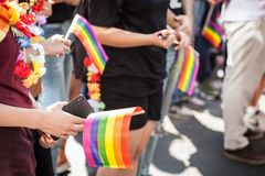 Hands of a girl holding a smartphone telephone with a camera and a rainbow gay flag during a Gay Pride. The rainbow flag is one of the symbols of the LGBTQ stock photography