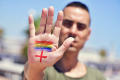 Rainbow flag and plus sign, for LGBTI HIV-positive people. Closeup of the a young caucasian man with a rainbow flag painted and a plus sign painted in the palm royalty free stock image