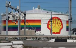 Rainbow flag and Shell logo on tank and pipes in the chemical industries in the Botlek Harbor in Rotterdam.  stock photography