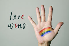 Rainbow flag and text love wins. Closeup of the palm of a young caucasian man with a rainbow flag painted in it and the text love wins, against an off-white stock image