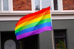 Rainbow flag waving in city at pride parade - LGBT symbol - for gay, lesbian, bisexual or transgender relationship, love or sexual. Ity - stock photo royalty free stock photos