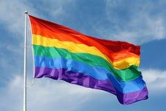 Rainbow flag waving proudly. Large rainbow flag proudly waving against the blue sunny skies royalty free stock images