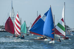 Rainbow fleet parade at Opera House Cup. A fleet of small colorful sails (the Rainbow Fleet} parade in front of Brant Point Lighthouse in Nantucket before the Royalty Free Stock Photography