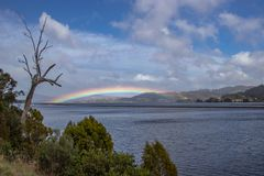 Rainbow over land at Kangaroo Bay, Tasmania stock photos