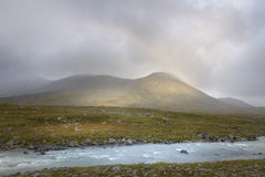 Rainbow forming in the rain clouds in autumn green landscape golden sunlight on mountains. Beautiful blue river raging in the autumn desolate landscape of Sarek Stock Photo