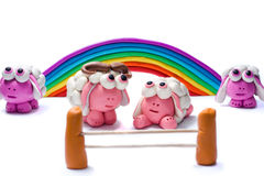 Rainbow and four plasticine sheep. Royalty Free Stock Images